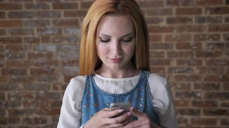 alluring : Young alluring blond girl is typing message on smartphone, brick background, communication concept
