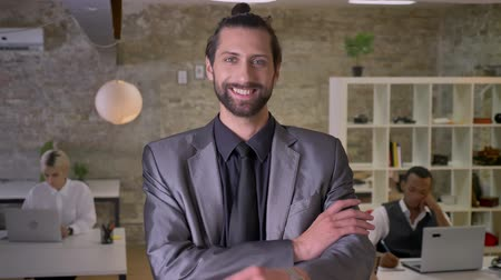 crossed : Happy businessman with beard is standing with arms crossed and watching at camera in office, smiling, colleagues are working with laptops, work concept