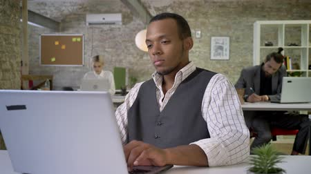 партнеры : Young african businesswoman is typing on laptop in office, colleagues are networking with technologies, work concept, communication concept Стоковые видеозаписи