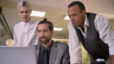 discutir : Three multy-ethnic workers discuss idea on laptop, coworking concept, communication concept Stock Footage