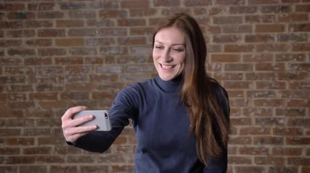 fool : Brown hair girl is making selfie on smartphone, fooling around, communication concept, brick background Stock Footage