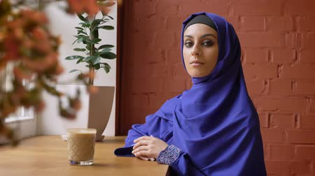 concerned girl : Young muslim woman in hijab sitting in cafe and looking at camera, serious beautiful female in headscarf Stock Footage