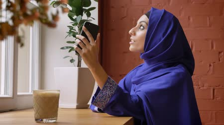 pronikavý : Young beautiful muslim woman in hijab having video chat through smartphone and smiling, sitting in cafe