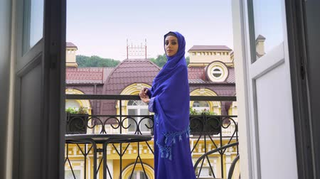 závoj : Young muslim woman in hijab standing on balcony, turning and looking at camera, beautiful female