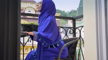 závoj : Young muslim woman in hijab going and sitting in chair on balcony, charming female relaxing