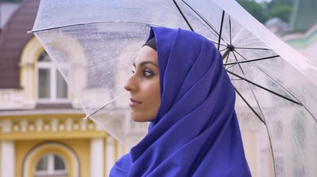 concerned girl : Profile of young muslim woman in hijab holding umbrella during rain, turning and looking at camera Stock Footage