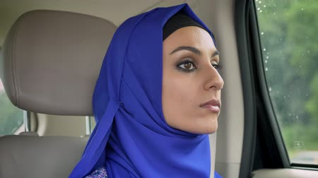 limuzína : Young muslim woman in hijab in car on passenger rear seat looking forward, serious