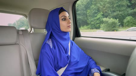 limuzína : Young beautiful muslim woman in hijab sitting in car on passenger rear seat