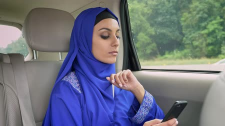 véu : Young muslim woman in hijab in car on passenger rear seat and typing on cell phone Vídeos