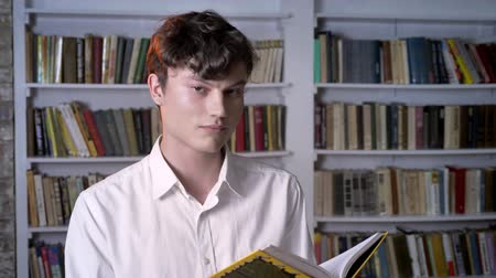 ders kitabı : Brunette man is reading book, watching at camera, library on background Stok Video