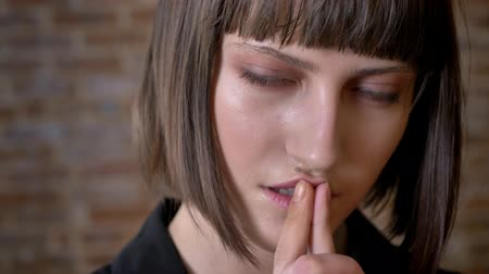 kısa : Young thoughtful woman with green eyes touching her lips looking at camera and sideways, brick background Stok Video