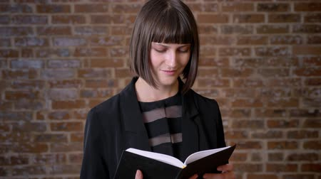 ansiklopedi : Young concentrated woman with short haircut reading book and standing near brick wall Stok Video