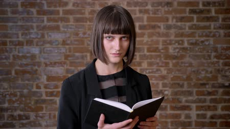 ansiklopedi : Young woman with short haircut reading book and smiling at camera, isolated on brick background Stok Video