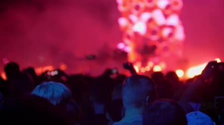 many lights : Heads of people standing at rock concert and listening, bright colorful illumination