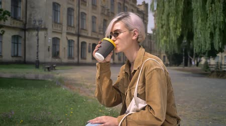 pronikavý : Trendy woman with pink hair in sunglasses drinking coffee and sitting near university