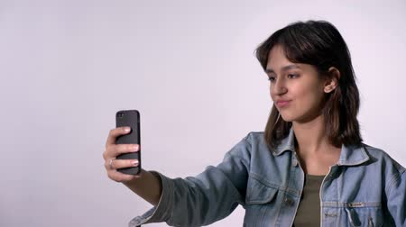 do widzenia : Young brunette girl has video call on smartphone, goodbye gesture, communication concept, white background