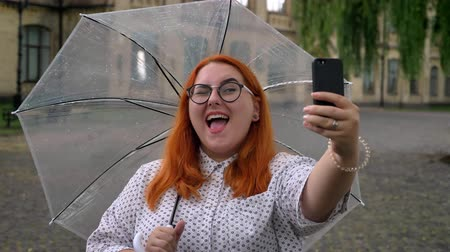 make photo : Fat ginger girl with glasses is making selfie on smartphone in park in rainy weather, winking, holding umbrella, communication concept