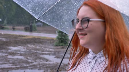 andar : Fat ginger girl with glasses is walking in park under rain, watching in sky holding umbrella, side view