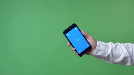 web design : Mans hand in white shirt showing mobile phone with chromakey in camera, chromakey background Stock Footage