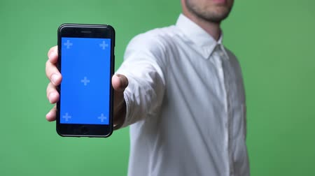 mock : Young man in white shirt showing phone with chromakey at camera, chromakey background Stock Footage