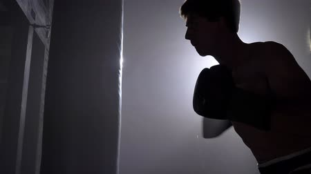 defending : Young boxer boxing in gloves, training in brick building Stock Footage
