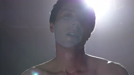 endure : Young sweaty exhausted man looking at camera and panting, smoke and bright illumination in background Stock Footage