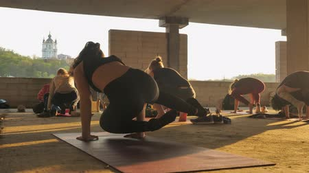 karga : People yogis are changing poses, standing on hands in abandoned building in summer on sunrise, healthy lifestyle, movement concept, sport concept