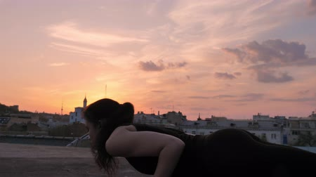 cobra : Yogi girl is standing in cobra pose on rooftop in summer on sunset, healthy lifestyle, relax concept, sport concept Stock Footage