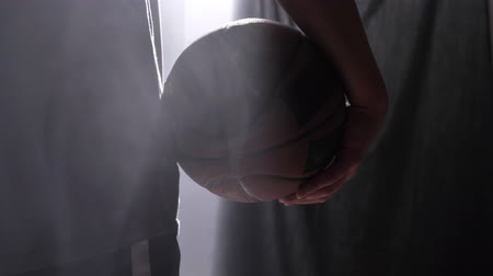 holding steady : Close footage of basketball player holding ball, standing in dark misty room Stock Footage