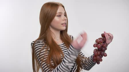 держит : Young sweet ginger girl is holding grape, throw one, watching at camera, white background