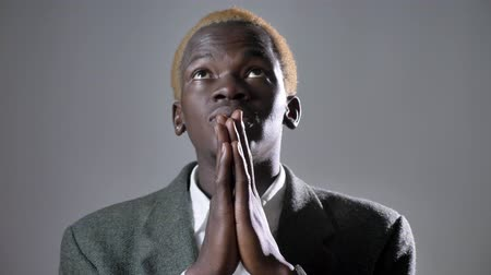 bossy : Young african american blond man in suit holding hands and praying, isolated on grey background