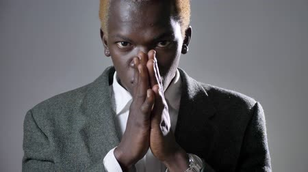 bossy : Young afro-american blond man in suit holding hands and praying, looking in camera, isolated on grey background Stock Footage