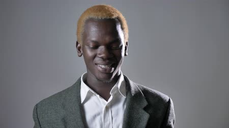 pronikavý : Young happy blond african man smiling at camera and touching face, isolated on grey background, successful businessman Dostupné videozáznamy