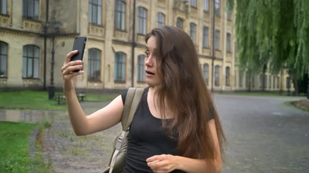 dizer : Caucasian beautiful woman having video chat through cell phone and talking, standing near university building on street