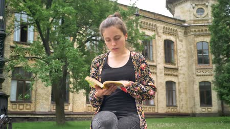 go to school : Young beautiful woman sitting and reading book, greeting somebody and going away, park near university background Stock Footage