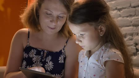 jegyzettömb : Mother with little daughter typing on tablet, sitting on couch at home, family concept indoors Stock mozgókép