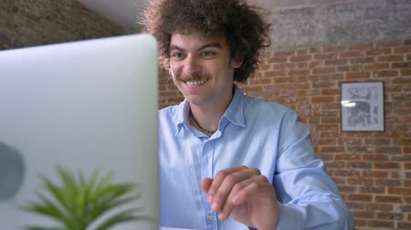computer programmer : Happy businessman with curly large hair cheering about victory, winner sitting at table with laptop, modern office background