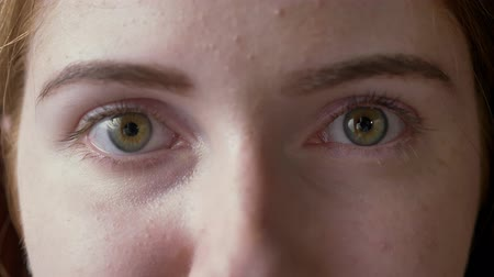 concerned girl : Close footage of young ginger woman green eyes looking at camera, macro shot Stock Footage