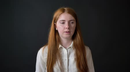 concerned girl : Thoughtful young ginger woman in white shirt deciding and worrying, isolated on black background Stock Footage