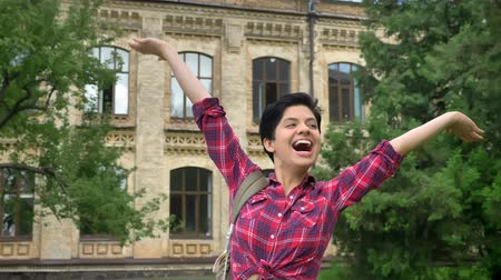 victory day : Cheerful young college student with short black hair cheering and smiling, standing in park near university Stock Footage