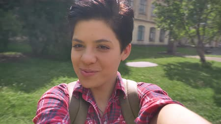 facetime : Cheerful happy college student recording video with selfie camera and turning around, smiling and laughing in park near university Stock Footage