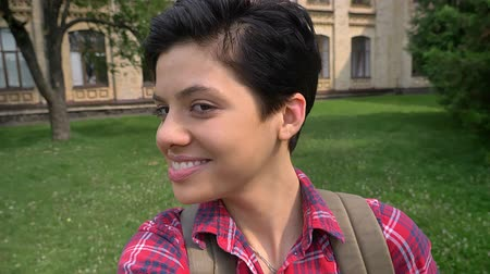 facetime : Cheerful young woman taking selfie and showing thumbs up, smiling and standing on grass in park near university Stock Footage