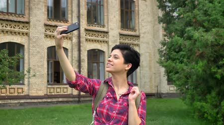 facetime : Charming happy college student with short black hair taking selfie and smiling, standing in park near university, cheerful