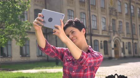 facetime : Young charming woman with short black hair taking selfie with table, standing on street near college, sunny weather