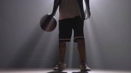 tatoo : One basketball player dribbling ball in misty dark room with floodlight