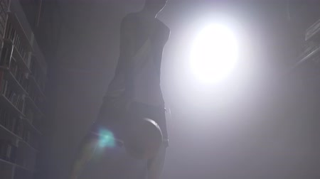tatoo : One basketball player silhouette playing with ball in misty dark room with floodlight Stock Footage