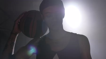 floodlight : Basketball player with tattoos holding ball on his shoulder and looking at camera