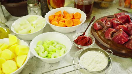 Ingredients for preparing Irish stew: beef, potatoes, carrots and herbs. Traditional St. Patricks day dish Стоковые видеозаписи