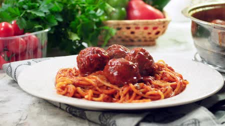 Serving spaghetti with meatballs in tomato sauce. 4K