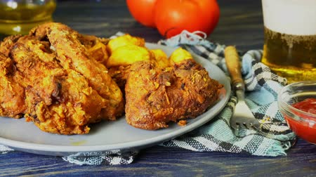 Crispy fried chicken wings with fried wedges on a plate. Breaded crispy chicken with baked potatoes for tasty dinner Стоковые видеозаписи